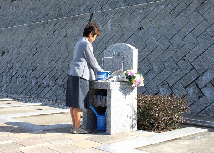 区画内に設置してある水場で水をくむ女性
